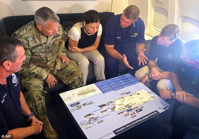 Acting Homeland Secretary Elaine Duke, center, is briefed on the Hurricane Maria response during a flight to Puerto Rico