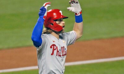 Bryce Harper of the Phillies is bailed out as he heads for his position against the Mets.