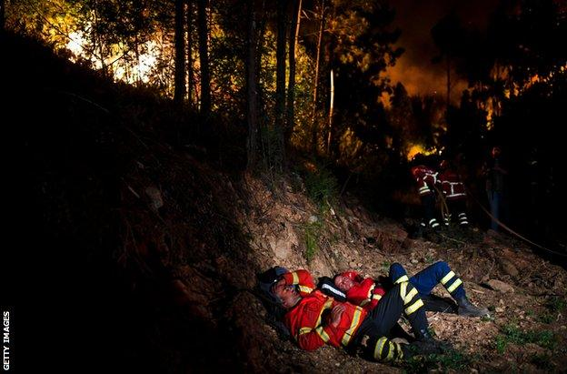 Firefighters take a break during a wildfire in central Portugal in June 2017.